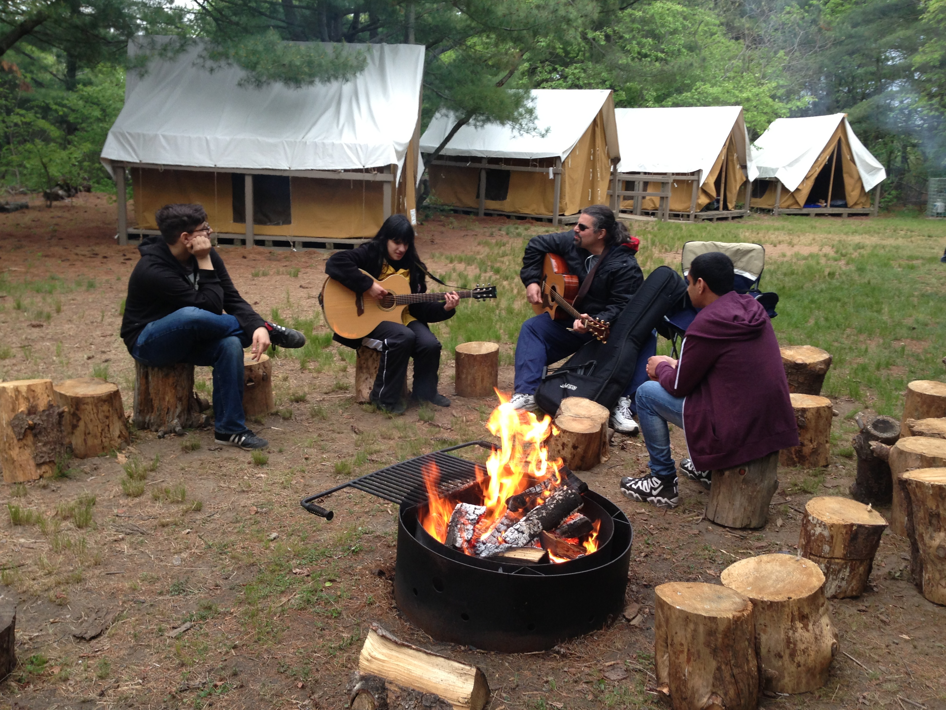 Photo of students and teacher sitting around a campfire, with one studetn and one teacher each playing a guitar.