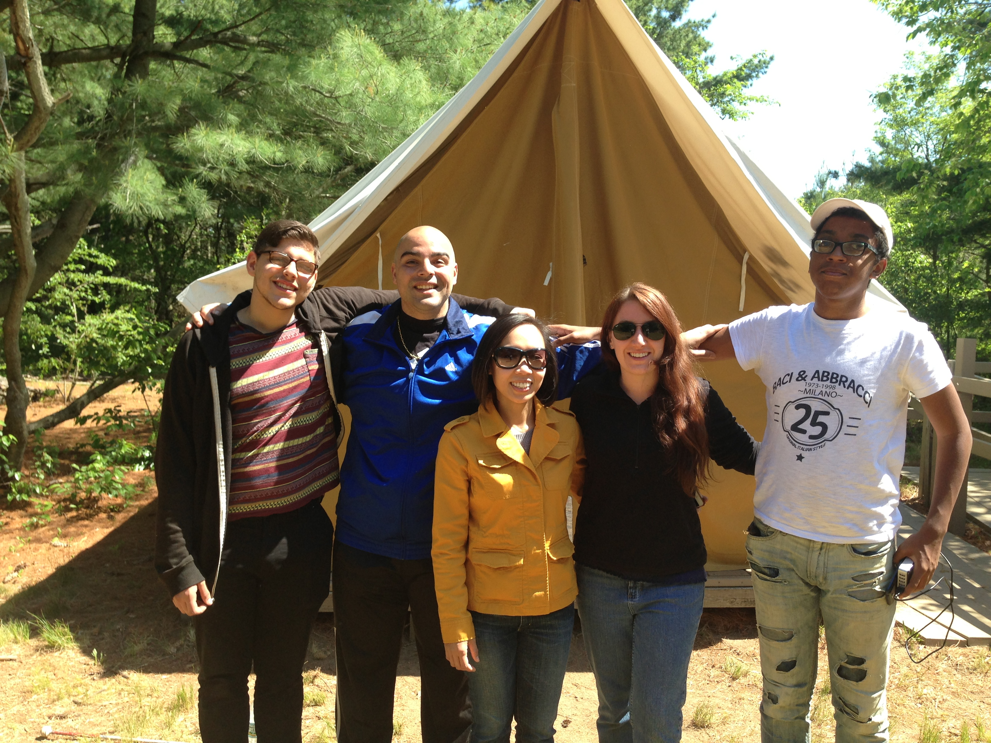 Photo of a group of five EVS students, teachers, and paras standing arm in arm in front of a tent.